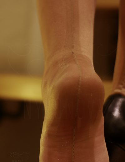 Mrs NyloNova wearing pencil skirt, beige super glossy Cuban Heel Gio Nylon Stockings. Black leather Kazar high heels.