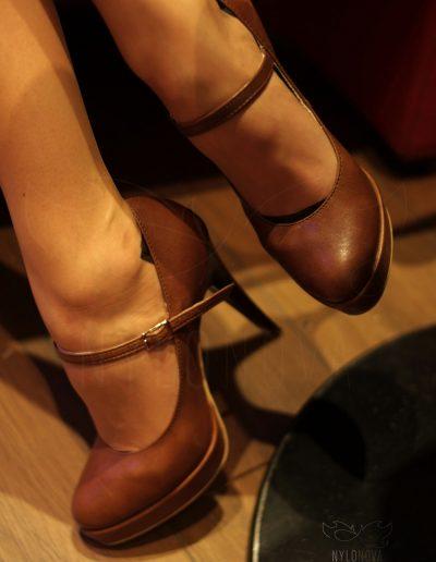 Mrs NyloNova wearing nude nylon stockings Eleganti in cinema waiting room. Contrast welt. Brown ankle strap high heels Aranci.