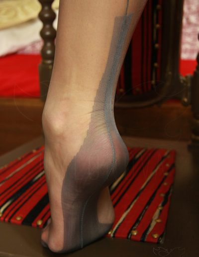 Mrs NyloNova is wearing grey Gio FF Cuban Heel nylon stockings, ankle strap high heels, pencil skirt and matching body.