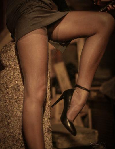 Mrs NyloNova wearing pencil skirt, grey glossy Cuban Heel Gio Nylon Stockings. Black leather Rylko ankle strap high heels.